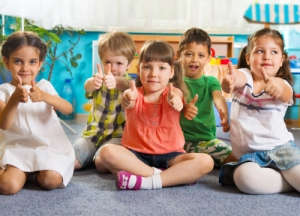 a group of pre-schoolers showing thumbs up