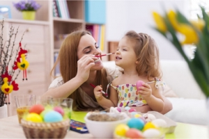 a woman amuse and tease the child happily with paintbrushes while designing easter eggs